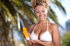 Frau, die in camera Flasche Sonnenblockcreme zeigt Lizenzfreies Stockbild