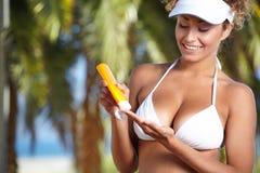 Frau, die in camera Flasche Sonnenblockcreme zeigt Stockfoto