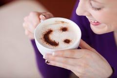 Frau, die Cappuccino im Café isst Lizenzfreie Stockfotografie