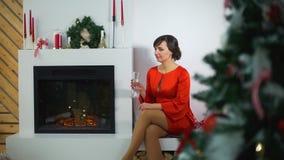 Frau, die Champagne Near der Kamin trinkt stock footage