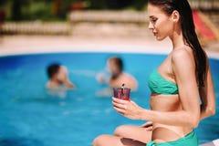 Frau, die Cocktail am Pool genießt stockfoto