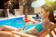 Frau, die Cocktail am Pool genießt stockbild