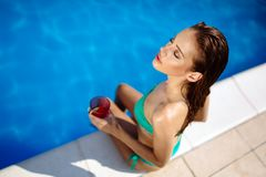 Frau, die Cocktail am Pool genießt lizenzfreie stockfotografie