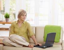 Frau, die Computer auf Couch verwendet stockbild