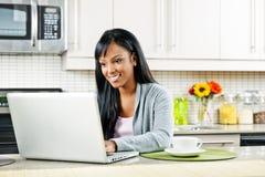 Frau, die Computer in der Küche verwendet Stockbild