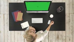 Frau, die am Computer in müdem trinkendem Kaffee des Büros arbeitet Grüne Schirm-Modell-Anzeige stock footage