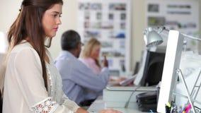 Frau, die Computer am Schreibtisch in beschäftigtem kreativem verwendet stock video footage