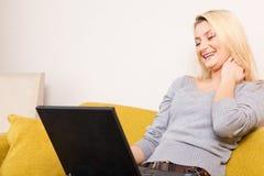 Frau, die Computer und das Lachen betrachtet Lizenzfreie Stockbilder