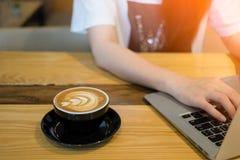 Frau, die Computerlaptop in der Kaffeestube verwendet Stockbild