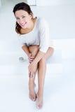 Frau, die Creme auf Beinen aufträgt stockfoto