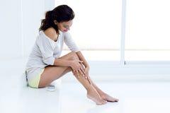 Frau, die Creme auf Beinen aufträgt Stockfotos