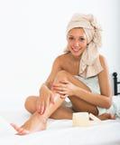 Frau, die Creme auf Füße setzt Lizenzfreies Stockfoto