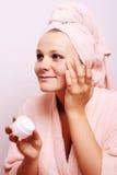 Frau, die Creme auf Gesicht anwendet Stockfotos