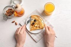 Frau, die dünne Pfannkuchen mit Beeren isst Stockbilder