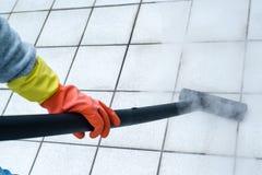 Frau, die Dampfreiniger verwendet Stockfoto