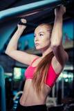 Frau, die das Anheben oben auf die Turnhallenstange tut Starkes recht weibliches in der Sportkleidung Lizenzfreie Stockfotografie