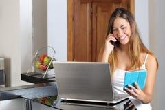 Frau, die das Arbeiten mit einer Laptoptablette und -telefon mehrere Dinge gleichzeitig tut Lizenzfreie Stockbilder