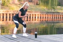 Frau, die das Ausdehnen durch den Fluss tut Stockfoto