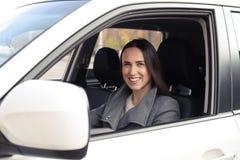 Frau, die das Auto und das Lächeln antreibt Stockfoto