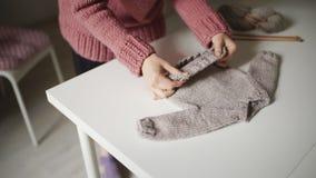 Frau, die das Baby betrachtet die gestrickte Strickjacke liegt auf Tabelle erwartet Handgemachte Kleidung stock footage