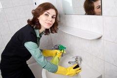 Frau, die das Badezimmer säubert Lizenzfreie Stockfotos