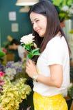 Frau, die das Blumenporträtlächeln hält Lizenzfreies Stockbild