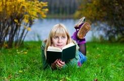 Frau, die das Buch auf dem Gras liest Lizenzfreie Stockfotografie