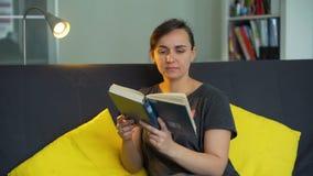 Frau, die das Buch in ihrem Appartement liest stock video footage