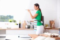 Frau, die das gesunde Lebensmittel steht macht, lächelnd in der Küche lizenzfreie stockfotos