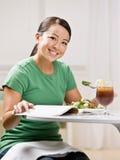 Frau, die das gesunde Mittagessen beim Lesen der Zeitschrift isst Stockbilder