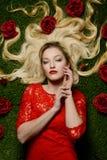 Frau, die in das Gras mit roten Rosen legt Stockfotografie