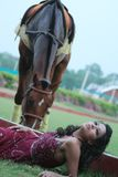 Frau, die in das Gras, nahe einem weiden lassenden Pferd legt. Stockfotografie