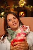 Frau, die das heiße Getränk setzt nahe Weihnachtsbaum und Kamin hält Stockfotos