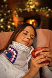 Frau, die das heiße Getränk setzt nahe Weihnachtsbaum und Kamin hat Stockbild