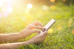 Frau, die das intelligente Mobiltelefon im Freien im Sonnenaufgang auf Natur verwendet lizenzfreies stockbild