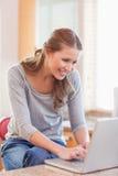 Frau, die das Internet in der Küche surft Stockbild