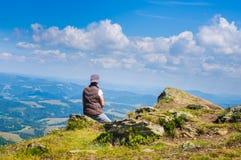 Frau, die das Karpaten-Mounta sitzt und betrachtet Stockfotografie