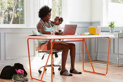 Frau, die das Kind zu Hause verwendet Computer nachdem dem Trainieren hält Stockfotos