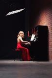 Frau, die das Klavier spielt stockbild