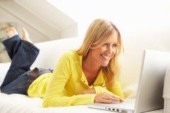 Frau, die das Laptop-entspannenc$sitzen auf Sofa verwendet Stockfoto
