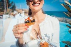 Frau, die das Lebensmittel an der Poolverpflegung im Strandhaus genießt Stockfotos