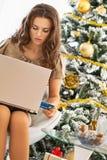 Frau, die das on-line-Einkaufen beim Sitzen nahe Weihnachtsbaum macht Stockfotos
