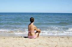 Frau, die das Meer überwacht Stockfotografie