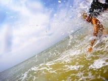 Frau, die in das Meer in den Tropen spritzt Stockbilder