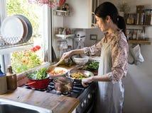 Frau, die das Mittagessen in einer Küche kocht lizenzfreies stockbild