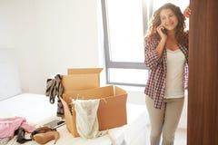 Frau, die in das neue Haus spricht am Handy umzieht Lizenzfreie Stockfotografie