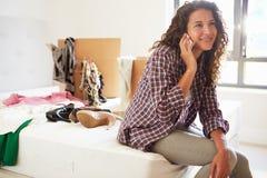 Frau, die in das neue Haus spricht am Handy umzieht Lizenzfreie Stockfotos