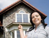 Frau, die das neue Haus zeigt Stockfotos