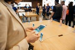 Frau, die das neue iPhone 7 Plustelefon betrachtet Lizenzfreie Stockbilder