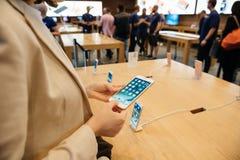 Frau, die das neue iPhone 7 Plustelefon betrachtet Lizenzfreie Stockfotos